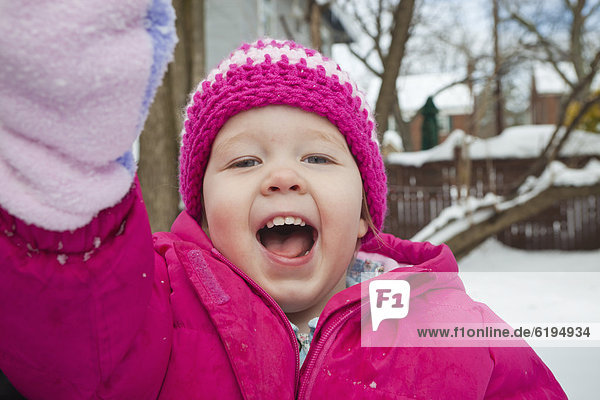 Grinning girl playing in snow