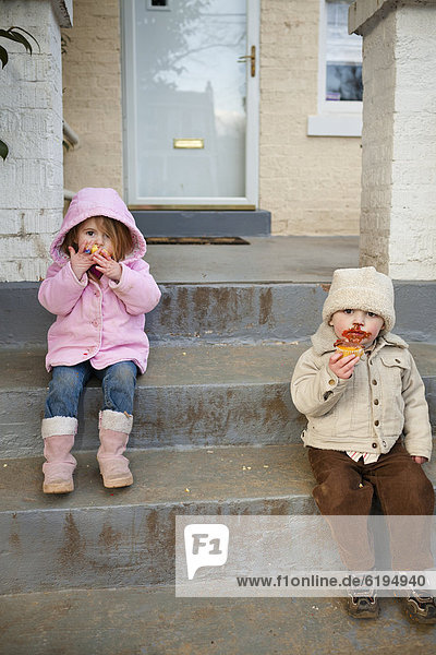 Caucasian brother and sister eating cupcakes on front stoop
