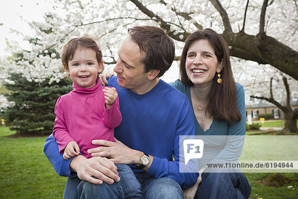 Caucasian family sitting together outdoors