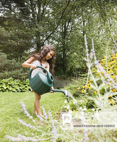 Hispanic girl watering garden