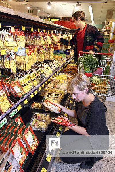 Kunden an Kühltheke mit frischen Nudeln  Pastaprodukte  Lebensmittelabteilung  Supermarkt  Deutschland  Europa