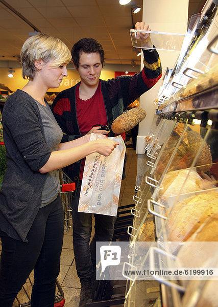Kundinnen an Selbstbedienungs-Brottheke  Lebensmittelabteilung  Supermarkt  Deutschland  Europa