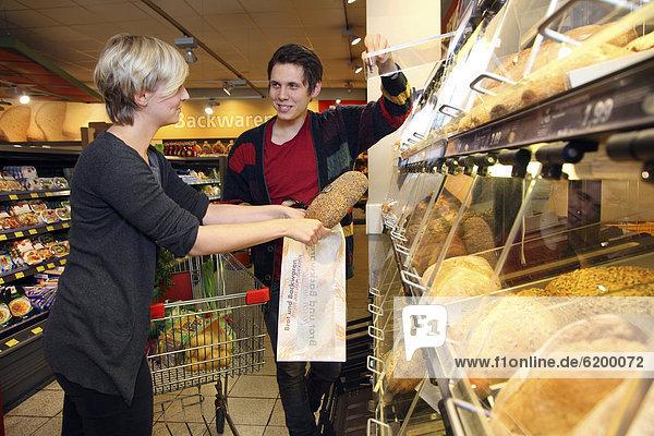 Kunden an Selbstbedienungs-Brottheke  Lebensmittelabteilung  Supermarkt  Deutschland  Europa