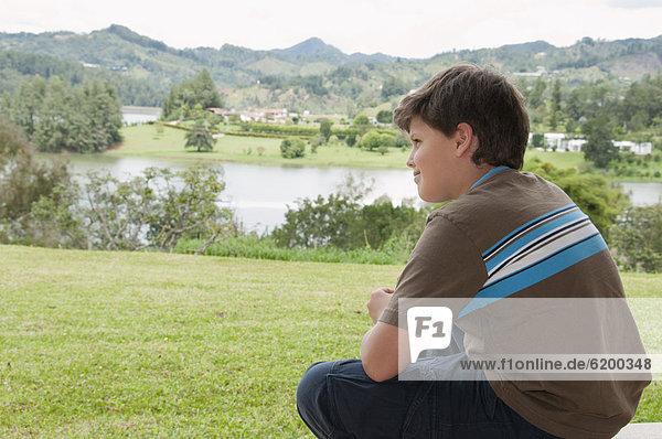 sitzend  Junge - Person  Hispanier  denken  Feld
