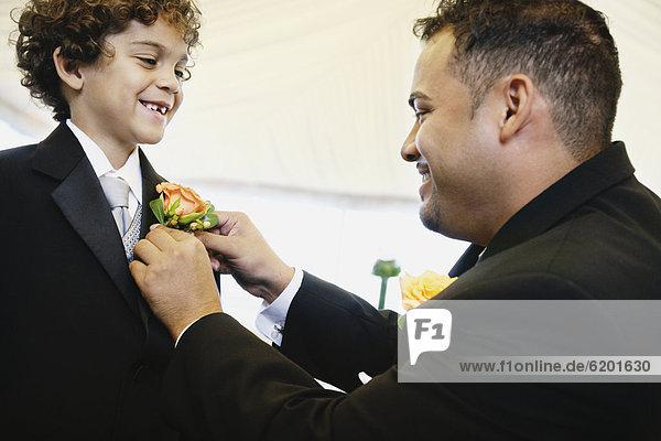 Menschlicher Vater  Sohn  Hispanier  befestigen  Ansteckblume
