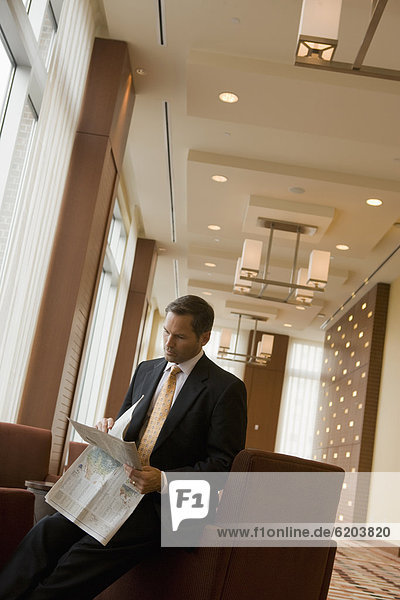 Businessman reading newspaper in lobby