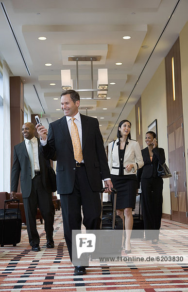 Multi-ethnic business people walking with suitcases down corridor