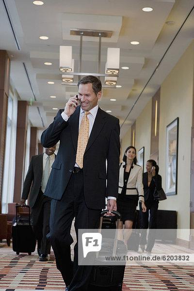 Handy  Korridor  Korridore  Flur  Flure  sprechen  Geschäftsmann  ziehen  Koffer
