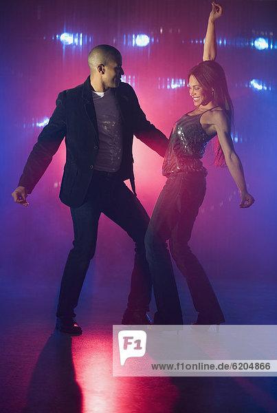 Boyfriend and girlfriend dancing at nightclub