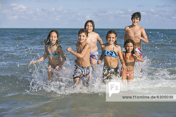 Hispanic children running through ocean surf