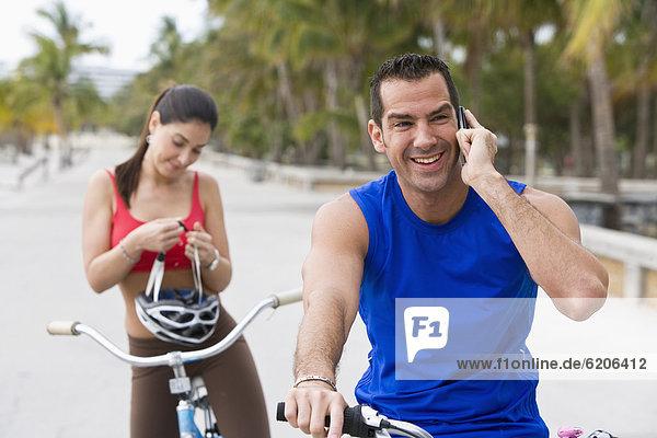 Handy  Mann  sprechen  Freundin  warten  Hispanier  Fahrrad  Rad