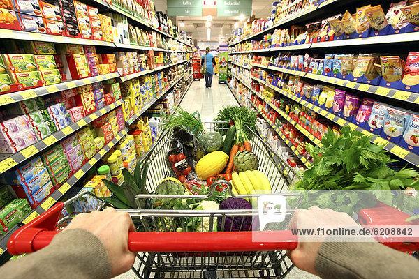 Voller Einkaufswagen wird durch einen Gang geschoben  Lebensmittelabteilung  Supermarkt  Deutschland  Europa