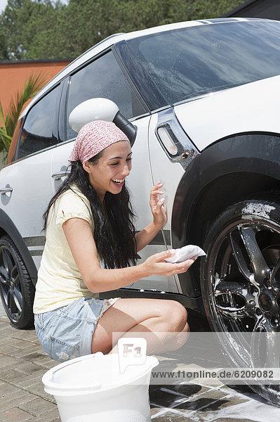 Frau lächeln Auto waschen Hispanier