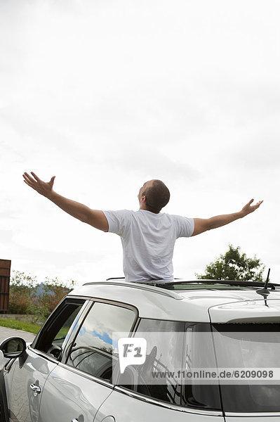 Dach  stehend  Mann  Hispanier  Arme ausbreiten  Arme ausstrecken  strecken  Sonne
