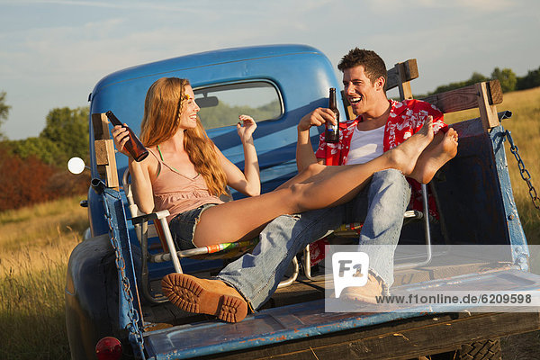 Caucasian couple drinking beer in back of truck