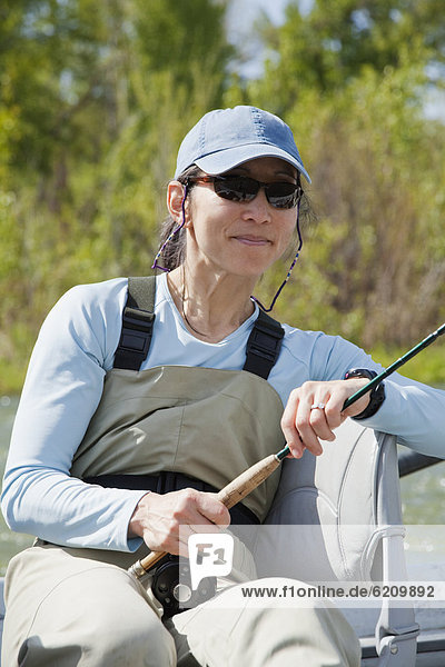Japanese American woman holding fly fishing pole