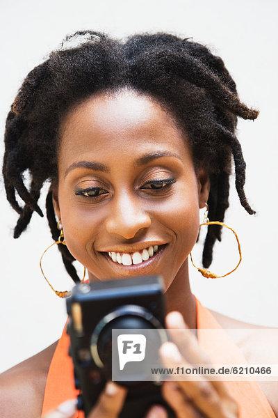 African woman holding digital camera