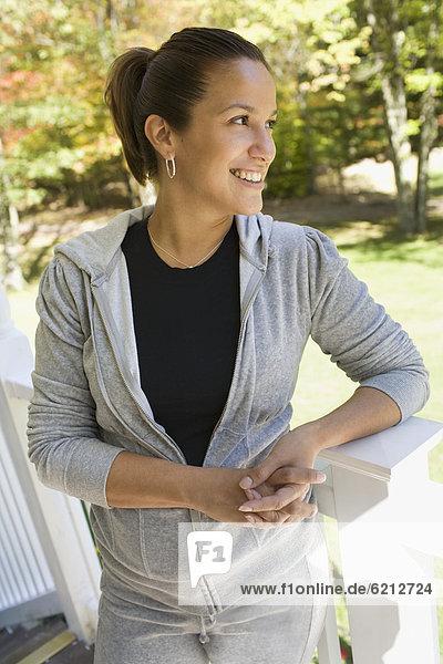 Hispanic woman leaning on railing
