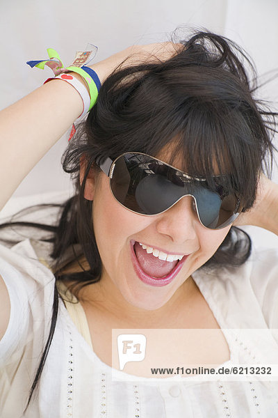Hispanic woman in sunglasses laughing