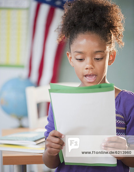 Mixed race girl reading report at school