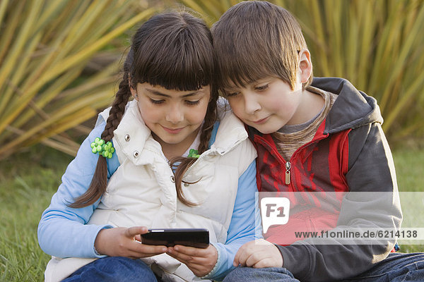 Chilean brother and sister looking at cell phone