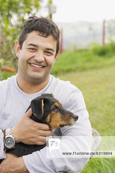Mann lächeln Hispanier halten Hund