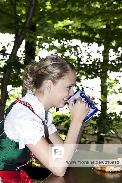 Young woman in a dirndl drinking beer in a beer garden at Pettstatt  Upper Franconia  Bavaria  Germany  Europe