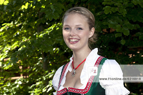 Young woman in a dirndl in a beer garden at Pettstatt  Upper Franconia  Bavaria  Germany  Europe