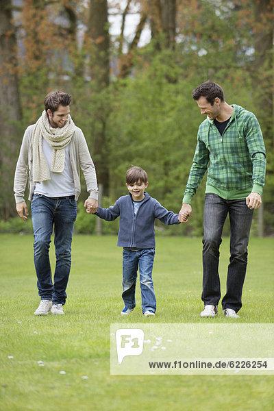 Junge  der mit zwei Männern in einem Park spazieren geht.