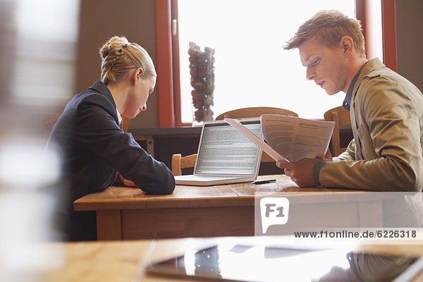 Business couple sitting in a restaurant and working