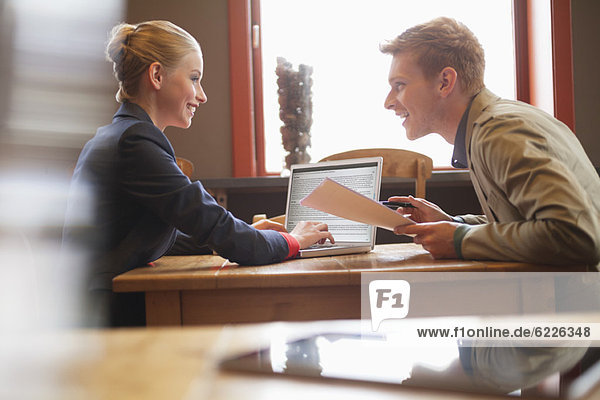 Paar sitzt in einem Restaurant und arbeitet an einem Laptop.