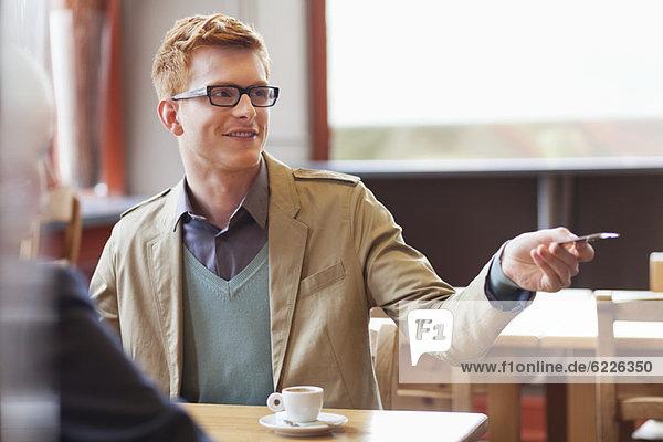 Mann  der die Rechnung per Kreditkarte in einem Restaurant bezahlt.