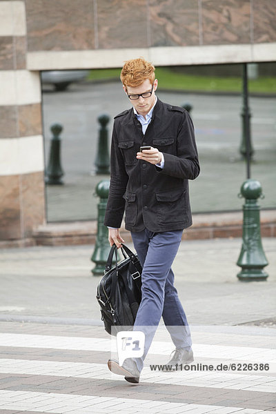 Geschäftsmann beim Überqueren einer Straße mit dem Handy