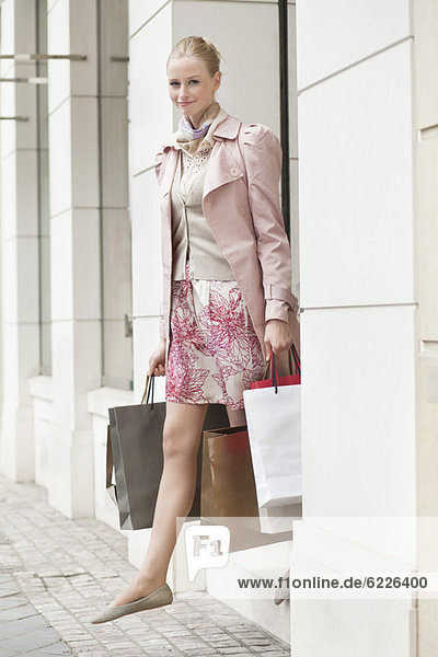 Woman exiting a store with shopping bags