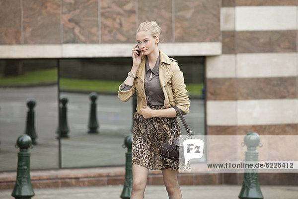 Geschäftsfrau beim Telefonieren über die Straße