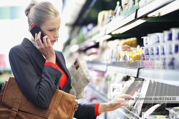 Frau im Supermarkt im Gespräch mit dem Handy