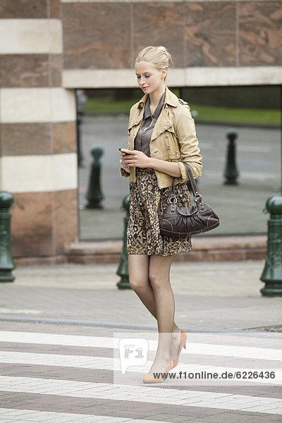 Geschäftsfrau beim Überqueren der Straße mit dem Handy