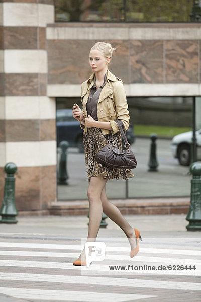 Geschäftsfrau beim Überqueren der Straße