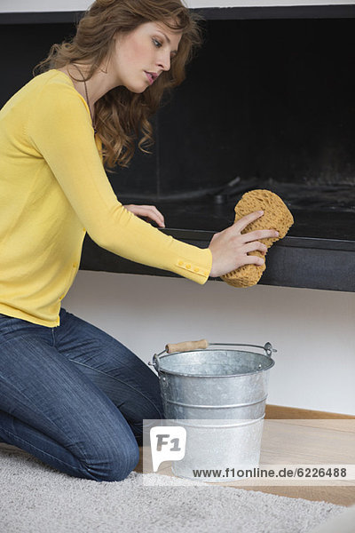 Frau beim Reinigen des Kamins