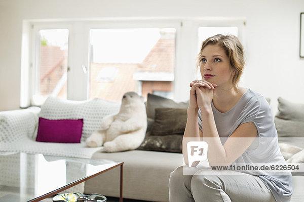 Frau sitzt auf einer Couch und schaut weg.