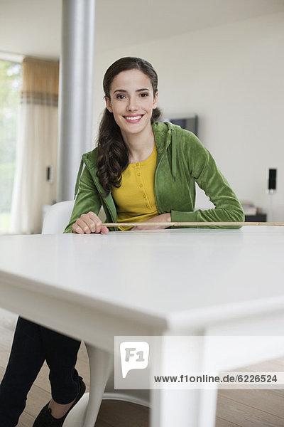 Glückliche Frau am Tisch sitzend