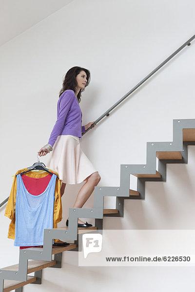 Frau  die die Treppe hinaufgeht und Kleidung trägt.