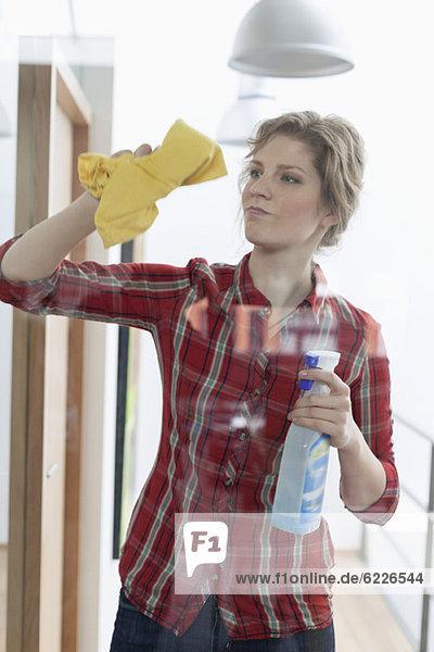Frau beim Reinigen einer Glastür