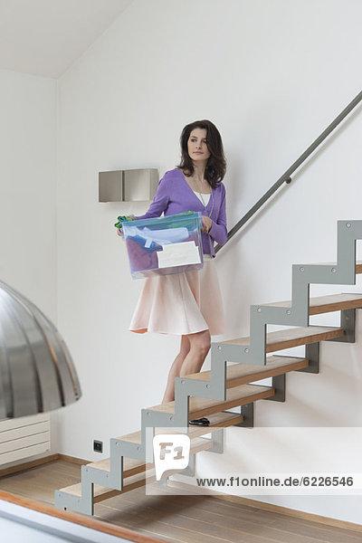 Frau  die eine Kiste mit Kleidung trägt.
