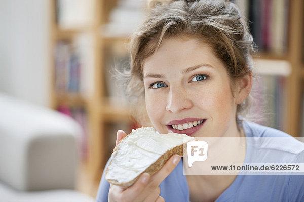 Porträt einer Frau beim Toastbrotessen mit Sahneaufstrich