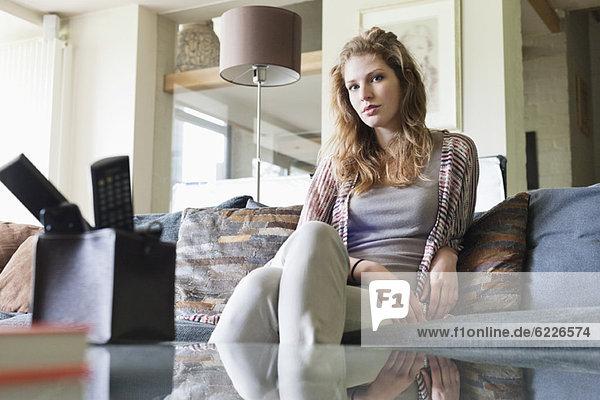 Porträt einer schönen Frau  die zu Hause auf einer Couch sitzt.
