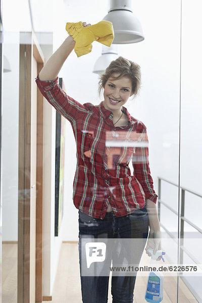 Frau putzt eine Glastür und lächelt