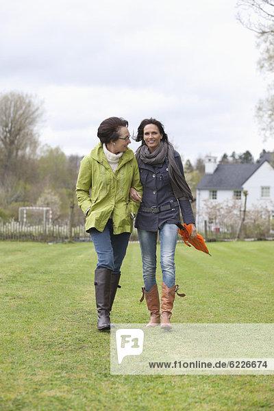 Zwei Frauen  die auf einem Rasen laufen.