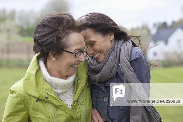 Zwei Frauen  die im Park lachen.