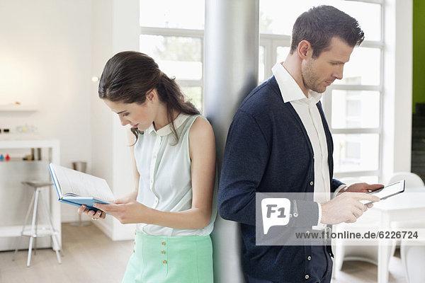 Mann  der ein elektronisches Buch benutzt  mit einer Frau  die ein Buch liest.